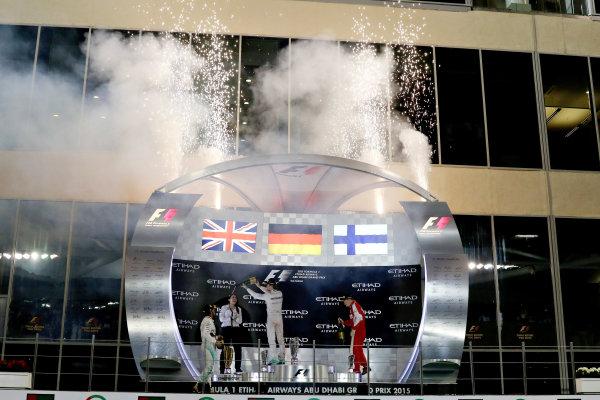Yas Marina Circuit, Abu Dhabi, United Arab Emirates. Sunday 29 November 2015. Nico Rosberg, Mercedes AMG, celebrates his win on the podium with Lewis Hamilton, Mercedes AMG, and Kimi Raikkonen, Ferrari. World Copyright: Glenn Dunbar/LAT Photographic ref: Digital Image 267A0185