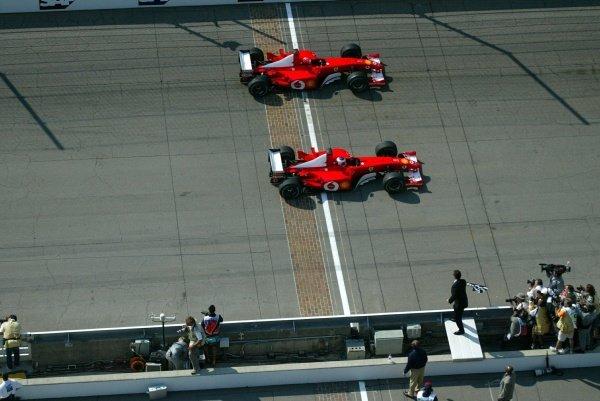 Rubens Barrichello (BRA, below) Ferrari F2002 inches past team mate Michael Schumacher (GER) Ferrari F2002 to take an unexpected victory. United States Grand Prix Race, Indianapolis, 29 September 2002. DIGITAL IMAGE