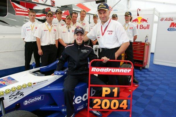 2004 Formula BMW ADAC champion Sebastian Vettel (GER), with Peter Mucke (GER), Team Owner Mucke Motorsport, and the team.  Formula BMW ADAC Championship 2004, Rd9 Race 2, Brno, Czech Republic. 19 September 2004.  DIGITAL IMAGE