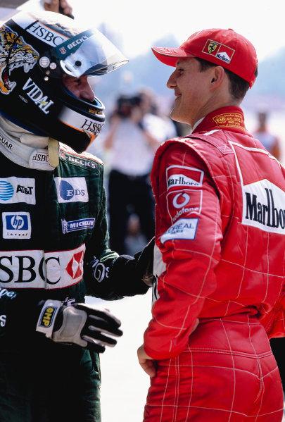 2002 Italian Grand PrixMonza, Italy. 14th - 16th September 2002Michael Schumacher, Ferrari F2002, congratulates Eddie Irvine, Jaguar Cosworth R3, on his 3rd place.World Copyright - LAT Photographicref: 35mm Transparency 02_ITA_32