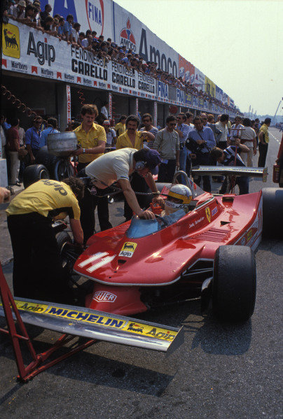 Jody Scheckter talks to engineers in the pitlane from his Ferrari 312T4.