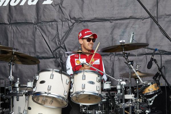 Red Bull Ring, Spielberg, Austria. Saturday 20 June 2015. Sebastian Vettel, Ferrari, tries his hand at drumming. World Copyright: Steve Etherington/LAT Photographic. ref: Digital Image SNE24029