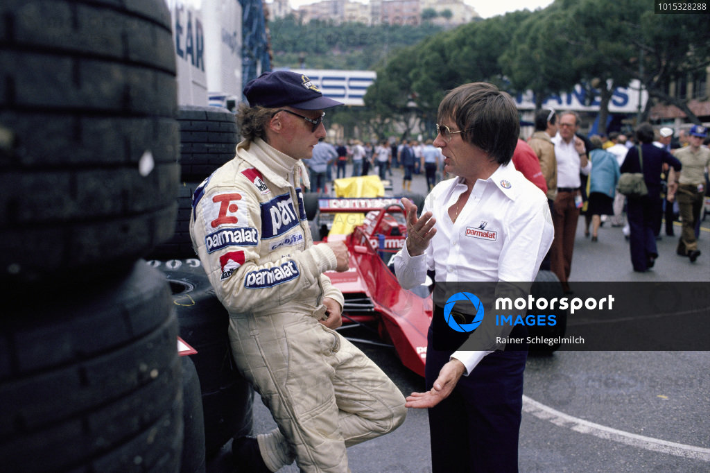 Niki Lauda and Bernie Ecclestone talk in the pits.