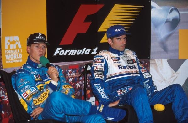 The stress on Michael Schumachers and Damon Hill's faces shows in a press conference.