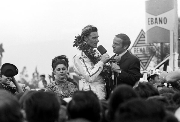 Race winner and World Champion for the second time Graham Hill (GBR) Lotus is interviewed by an ABC Television commentator on the podium. Mexican Grand Prix, Mexico City, 3 November 1968.