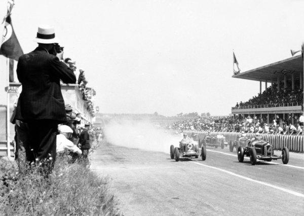 "1934 Marne Grand Prix Reims, France. 8 July 1934 Achille Varzi, Alfa Romeo Tipo-B ""P3"", leads Philippe Etancelin, Maserati 8CM, Guy Moll, Alfa Romeo Tipo-B ""P3"", Louis Chiron, Alfa Romeo Tipo-B ""P3"", Goffredo Zehender, Maserati 8CM, and Renato Balestrero, Alfa Romeo 8C ""Monza"", at the start, action World Copyright: Robert Fellowes/LAT PhotographicRef: 34REI04"