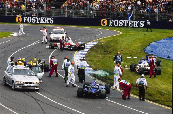 The opening corner melee is cleared up by marshals. Involved are Giancarlo Fisichella, Jordan EJ12 Honda, Allan McNish, Toyota TF102, Felipe Massa, Sauber C21 Petronas, Olivier Panis, BAR 004 Honda, and Nick Heidfeld, Sauber C21 Petronas.