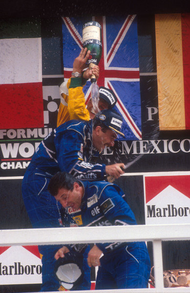 1992 Mexican Grand Prix.Mexico City, Mexico.20-22 March 1992.Nigel Mansell, 1st position and Riccardo Patrese 2nd position (both Williams Renault) get showered with champagne from Michael Schumacher (Benetton Ford) 3rd position on the podium.Ref-92 MEX 02.World Copyright - LAT Photographic