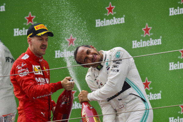 Sebastian Vettel, Ferrari, 3rd position, and Lewis Hamilton, Mercedes AMG F1, 1st position, spray Champagne on the podium