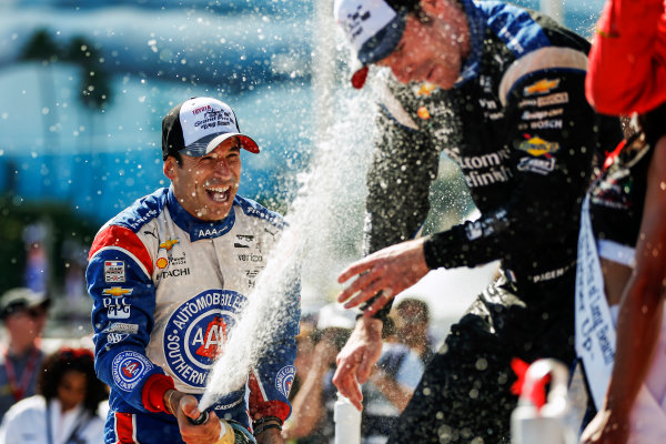 15-17 April, 2016, Long Beach, California USA 3 Helio Castroneves celebrates with champagne on the podium with 22 Simon Pagenaud ?2016, Sam Cobb LAT Photo USA