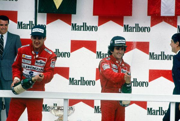 Mexico City, Mexico. 27th - 29th May 1988.Ayrton Senna (McLaren MP4/4 Honda), 2nd position and Alain Prost (McLaren MP4/4 Honda) 1st position, celebrate on the podium, portrait. World Copyright: LAT Photographic.Ref:  88MEX04