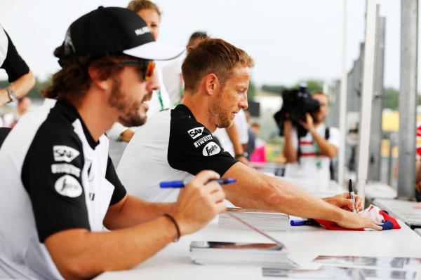 Hungaroring, Budapest, Hungary. Thursday 23 July 2015. Fernando Alonso, McLaren, and Jenson Button, McLaren, sign autographs for fans. World Copyright: Charles Coates/LAT Photographic ref: Digital Image _J5R0855