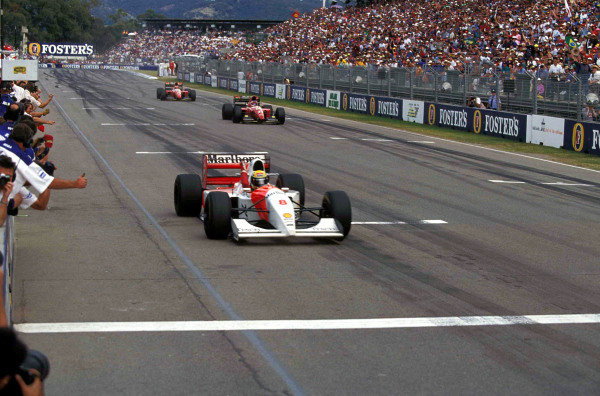 Ayrton Senna, McLaren MP4-8 Ford, raises his arm as he crosses the line at the end of the race ahead of Jean Alesi, Ferrari F93A, and Gerhard Berger, Ferrari F93A.