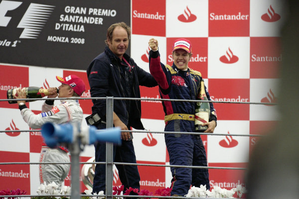 Sebastian Vettel celebrates victory on the podium with team boss Gerhard Berger.