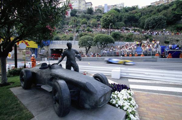 A Renault R23 passes a statue of Juan Manuel Fangio stood beside a Mercedes W196.