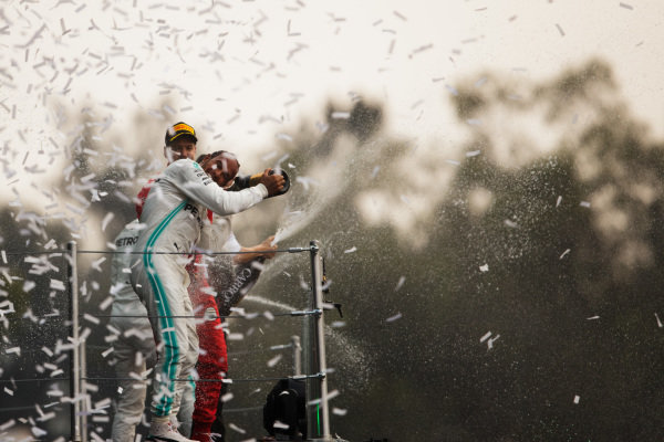 Lewis Hamilton, Mercedes AMG F1, 1st position, and Sebastian Vettel, Ferrari, 2nd position, spray each other with Champagne on the podium
