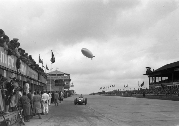 Luigi Villoresi, Maserati 8CTF, comes into the pits to make a stop as a Graf Zeppelin, LZ 130, flies overhead.