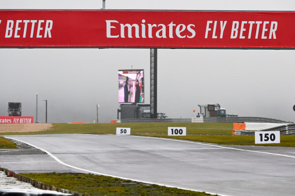 A track side screen in use as rain lashes the circuit