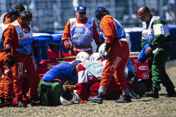 Medical staff and Marshals attend to Michael Schumacher, Ferrari F399. The German driver broke his leg in the accident which would see him sidelined until the penultimate round in Malaysia.
