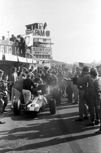 Colin Chapman (GBR) Lotus Team Owner holds a pit board between Jim Clark (GBR) and the Coventry Climax engine powering his Lotus 33 as Clark makes the first of two late pit stops to top the car with water, dropping his from second to third place as a result. Dutch Grand Prix, Zandvoort, 24 July 1966.