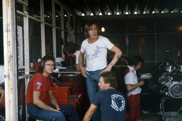 McLaren teammates James Hunt and Jochen Mass wait in the garage with Barry Sheene.