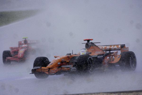 Adrian Sutil, Spyker F8-VII Ferrari sliding into the gravel in the wet conditions as Kimi Räikkönen, Ferrari F2007 keeps on track.