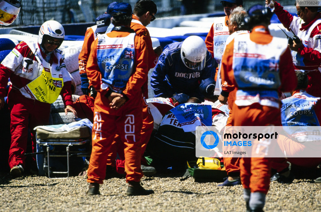 Doctors and marshals attend to Michael Schumacher, Ferrari F399, after he crashed heavily at Stowe corner following a brake failure. The resulting leg injuries sidelined him for the next six races.