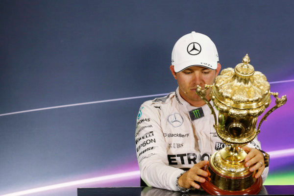 Silverstone Circuit, Northamptonshire, England. Sunday 5 July 2015. Nico Rosberg, Mercedes AMG, 2nd Position, inspects the trophy of Lewis Hamilton, Mercedes AMG, 1st Position, in the Press Conference. World Copyright: Alastair Staley/LAT Photographic ref: Digital Image _R6T7616