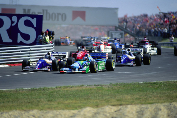 Michael Schumacher, Benetton B194 Ford, leads Damon Hill, Williams FW16B Renault, David Coulthard, Williams FW16B Renault, and Gerhard Berger, Ferrari 412T1B, at the start.