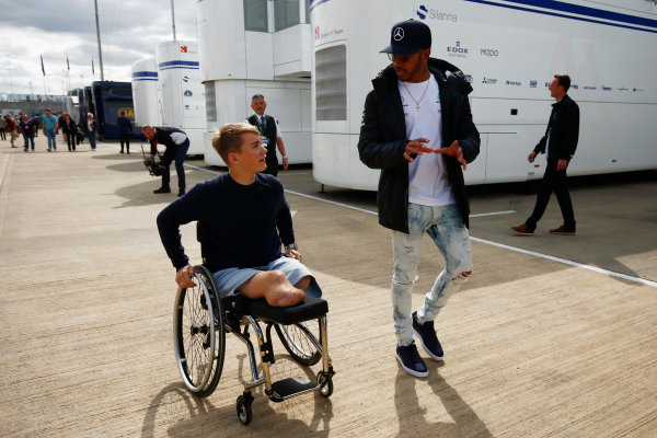Silverstone, Northamptonshire, UK.  Friday 14 July 2017. Lewis Hamilton, Mercedes AMG, talks to recovering British Formula 4 driver Billy Monger in the paddock. World Copyright: Andy Hone/LAT Images  ref: Digital Image _ONY6366