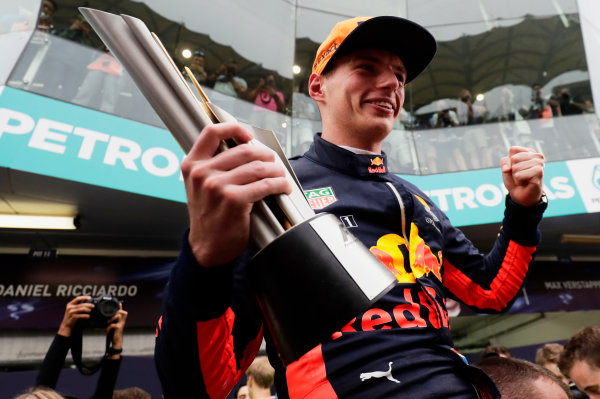 Sepang International Circuit, Sepang, Malaysia. Sunday 01 October 2017. Max Verstappen, Red Bull Racing, lifts his winner's trophy as he is hoisted into the air by mechanics. World Copyright: Zak Mauger/LAT Images  ref: Digital Image _56I3763