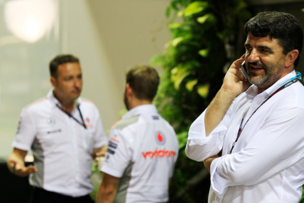 Marina Bay Circuit, Singapore. Friday 20th September 2013. Luis Garcia Abad, Manager of Fernando Alonso talks on a mobile phone near the McLaren team in the paddock. World Copyright: Charles Coates/LAT Photographic. ref: Digital Image _X5J8926
