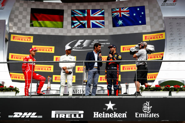 Spa Francorchamps, Belgium.  Sunday 27 August 2017. Sebastian Vettel, Ferrari, 2nd Position, and Lewis Hamilton, Mercedes AMG, 1st Position, look on as Mark Webber interviews Daniel Ricciardo, Red Bull Racing, 3rd Position, on the podium. World Copyright: Sam Bloxham/LAT Images  ref: Digital Image _J6I0280