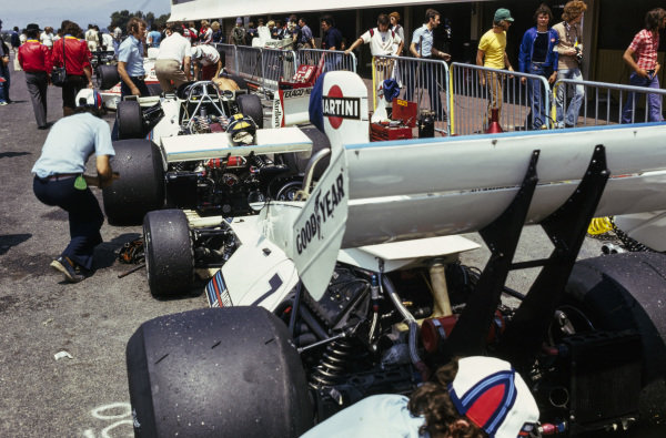 Mechanics work on the Brabham BT44B Ford cars of Carlos Pace and Carlos Reutemann in the pitlane. Pace's helmet rests on the rear wing of his car.
