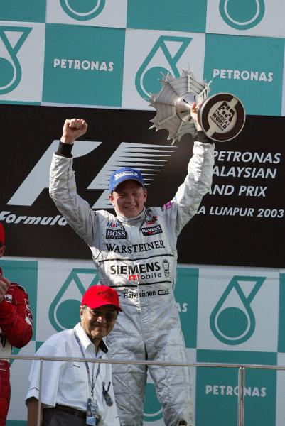 2003 Malaysian Grand Prix. Sepang, Kuala Lumpur, Malaysia.21-23 March 2003.Kimi Raikkonen (McLaren Mercedes) celebrates his 1st position and maiden Grand Prix win on the podium.World Copyright - Steve Etherington/LAT Photographic ref: Digital Image Only