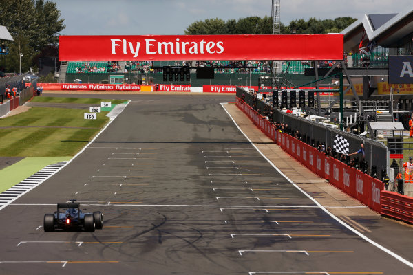 2016 British Grand Prix. Silverstone, Northamptonshire, UK. Sunday 10 July 2016. Lewis Hamilton, Mercedes F1 W07 Hybrid takes the chequered flag as he crosses the finish. World Copyright: Ferraro/LAT Photographic ref: Digital Image _40I5011