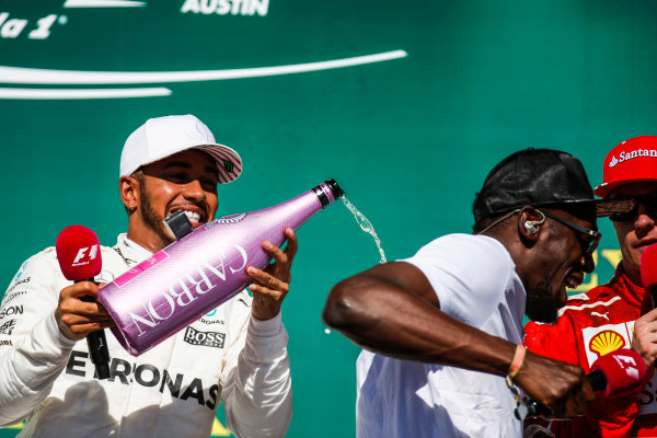 Circuit of the Americas, Austin, Texas, United States of America. Sunday 22 October 2017. Lewis Hamilton, Mercedes AMG, sprays the champagne with Usain Bolt on the podium. World Copyright: Zak Mauger/LAT Images  ref: Digital Image _X0W7238