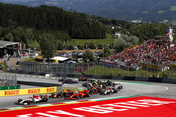 Kimi Raikkonen, Alfa Romeo Racing C38, leads Sebastian Vettel, Ferrari SF90, Max Verstappen, Red Bull Racing RB15, Pierre Gasly, Red Bull Racing RB15, Antonio Giovinazzi, Alfa Romeo Racing C38, and the remainder of the field at the start