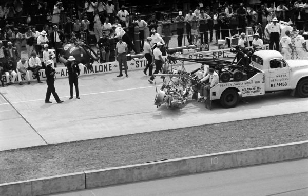 A burnt car is returned to the pits.