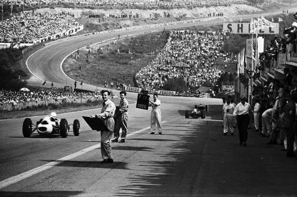 View from the pits looking down hill towards Eau Rouge, as mechanics hold pitboards to signal to drivers.