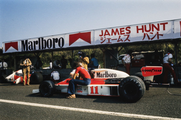 James Hunt, McLaren M23 Ford, talks to Teddy Mayer and Barry Sheene, in the pit lane.