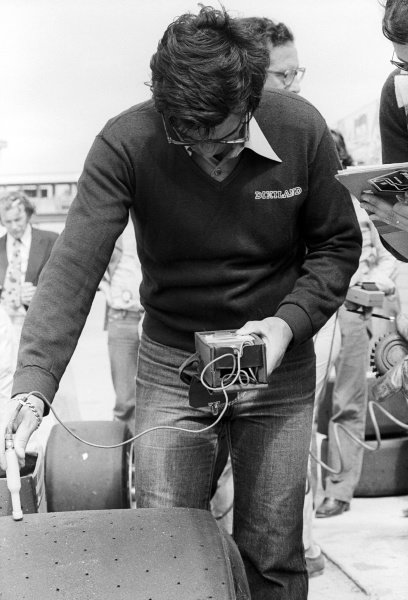 A Michelin tyre technician checks the temperature of a tyre on a Ferrari 312T3 in the pits.Formula One Testing, Brands Hatch, England, c. June 1978.