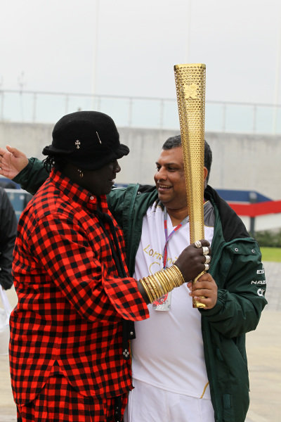 Mr Moko (SEN) Chrome Hearts Jewellery and Tony Fernandes (MAL) Caterham Team Principal with the Olympic Torch. Formula One World Championship, Rd9, British Grand Prix, Race, Silverstone, England, Sunday 8 July 2012.