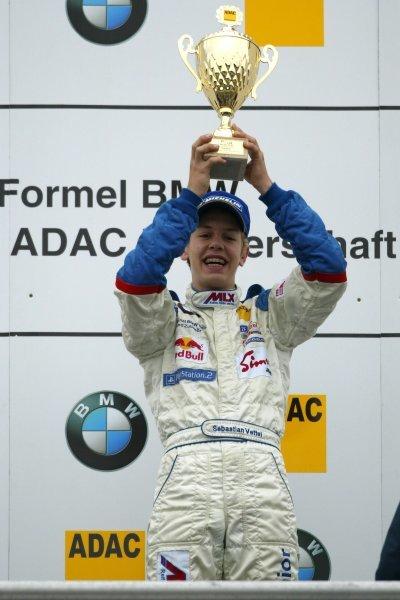 Race winner Sebastian Vettel (GER), Eifelland Racing, holding up the winners trophy on the podium.Formula BMW ADAC Championship, Rd20, Hockenheim, Germany. 5 October 2003. DIGITAL IMAGE