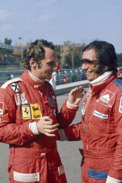 Niki Lauda talks to Emerson Fittipaldi in the pitlane.