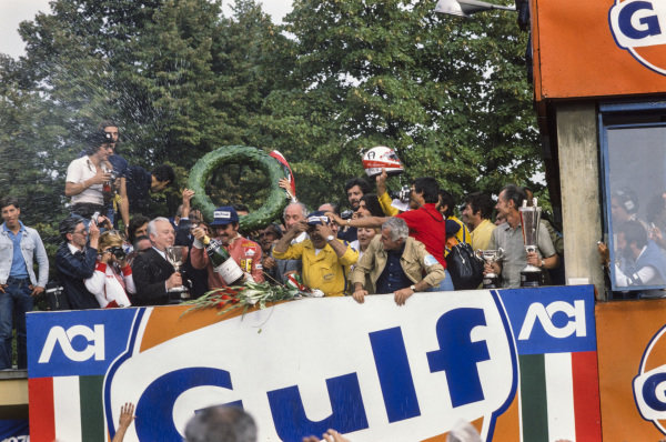 Clay Regazzoni celebrates victory on the podium with members of his team.