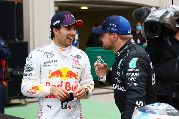 Sergio Perez, Red Bull Racing, 3rd position, and Valtteri Bottas, Mercedes, 1st position, talk in Parc Ferme