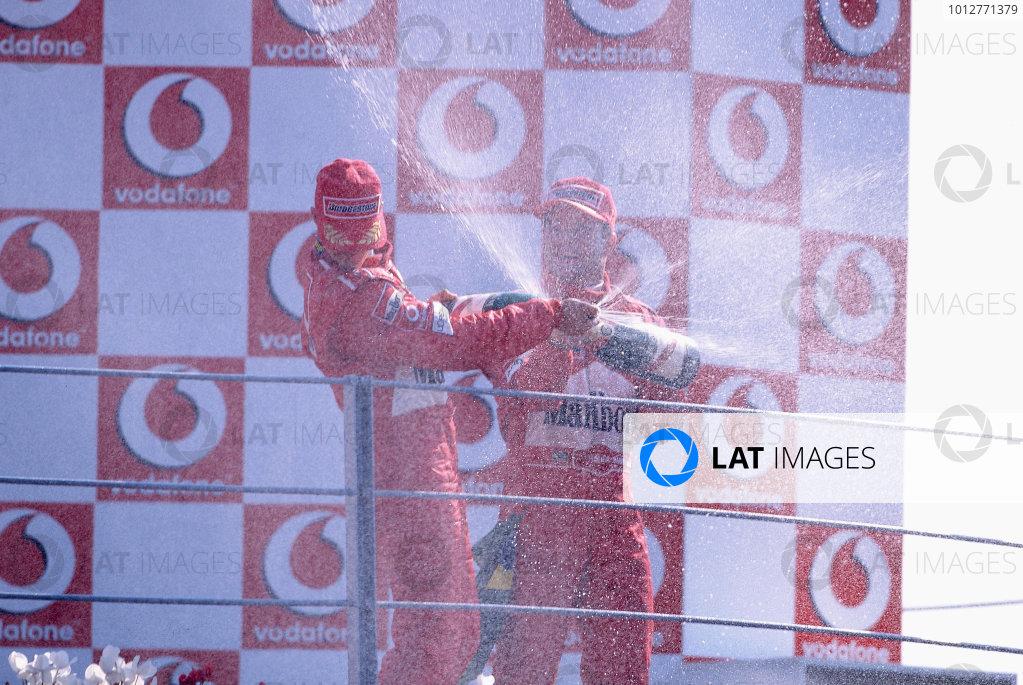 2002 Italian Grand PrixMonza, Italy. 14th - 16th September 2002Rubens Barrichello, Ferrari F2002, and Michael Schumacher, Ferrari F2002, on the podium spraying champagne.World Copyright - LAT Photographicref: 35mm Transparency 02_ITA_38