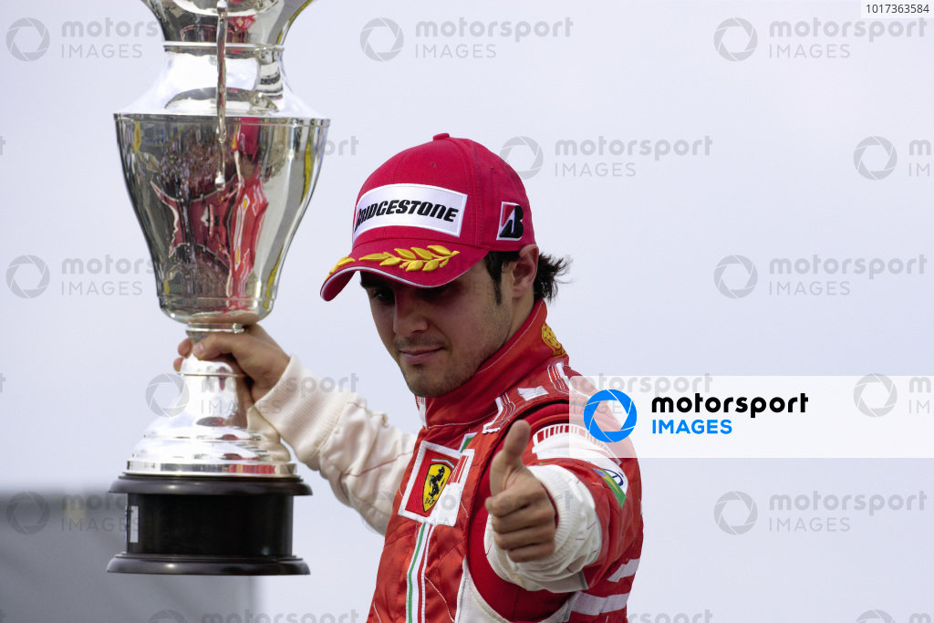 2nd placed Felipe Massa holds up his trophy and gives a thumbs up to his team below.