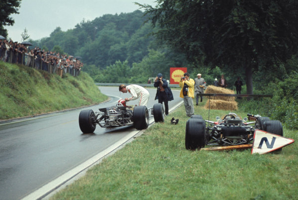 1968 French Grand Prix. Rouen-les-Essarts, France. 5-7 July 1968. Graham Hill (Lotus 49 Ford) who had retired, gives his teammate Jo Siffert (Lotus 49 Ford) his visor on the trackside. Ref-68 FRA 03. World Copyright - LAT Photographic